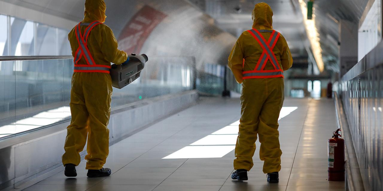 Airport is being disinfected by workers in hazmat suits