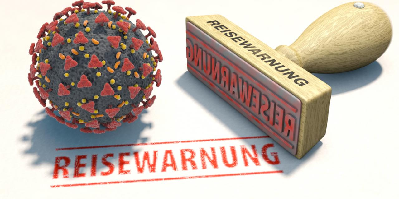 "Model of the coronavirus next to stamp with ""travel warning"" imprint"