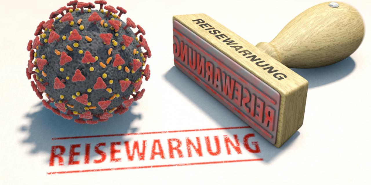 """Model des Coronavirus neben Stempel mit Aufdruck """"Reisewarnung"""""""