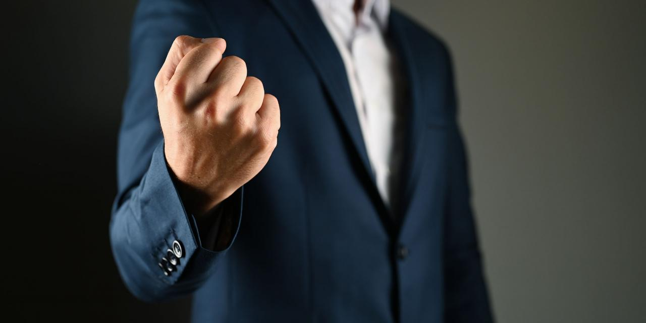 Drohgebärde mit Faust durch einen Mann im Anzug