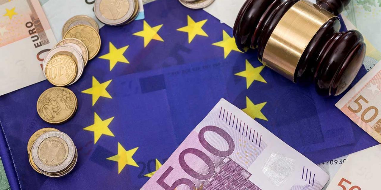 Euroscheine und Münzen sowie ein Gerichtshammer liegen auf Europaflagge