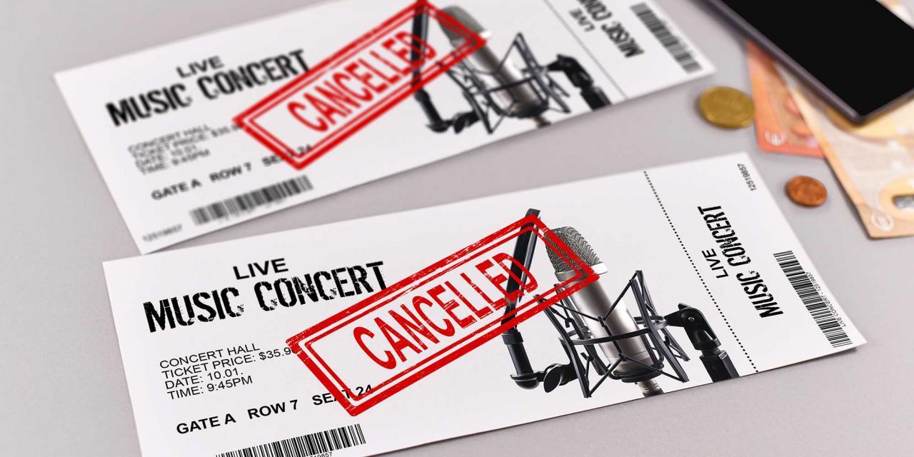 """Musiktickets mit dem Aufdruck """"Cancelled"""", daneben Geld und Smartphone"""