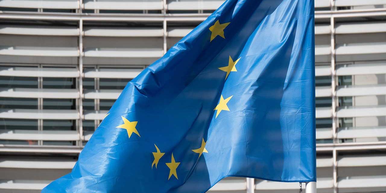 EU Fahne weht vor einem modernen Gebäude