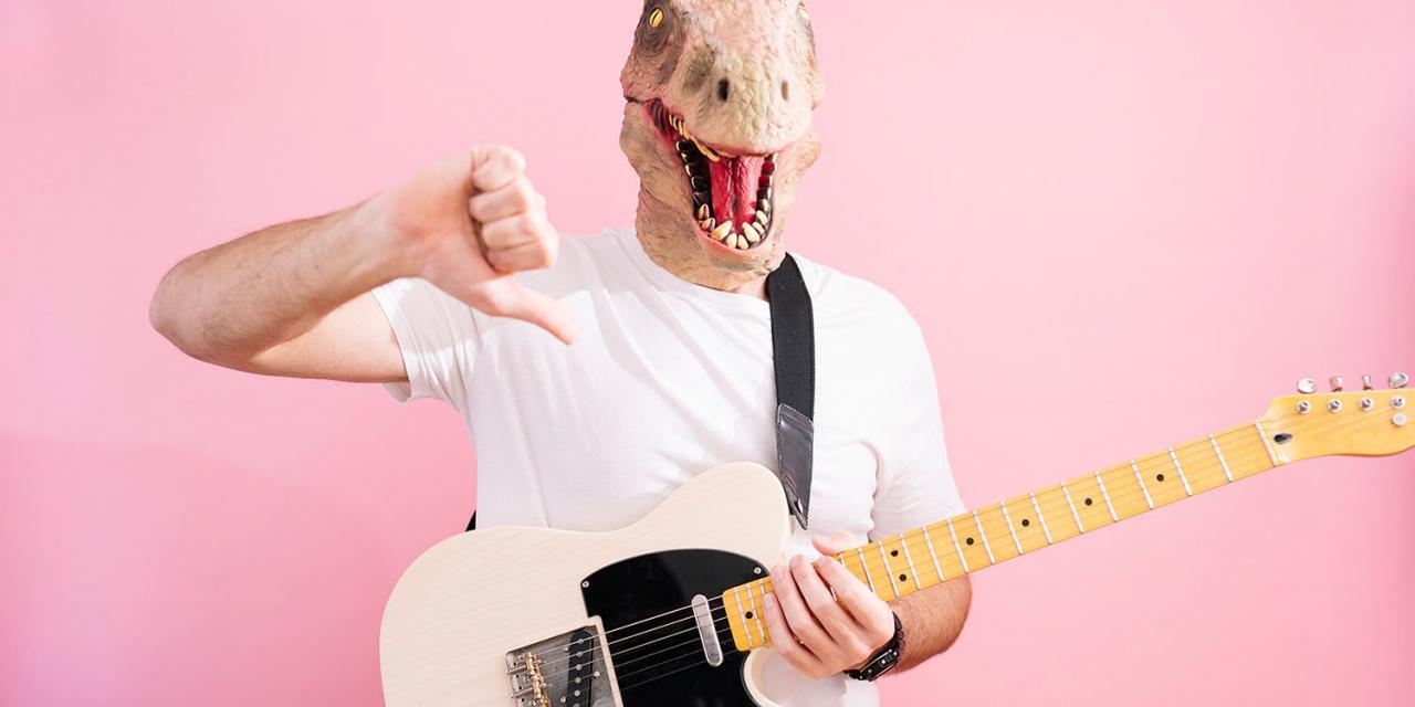 Mann mit Dinomaske und umgehängter Gitarre deutet Daumen runter