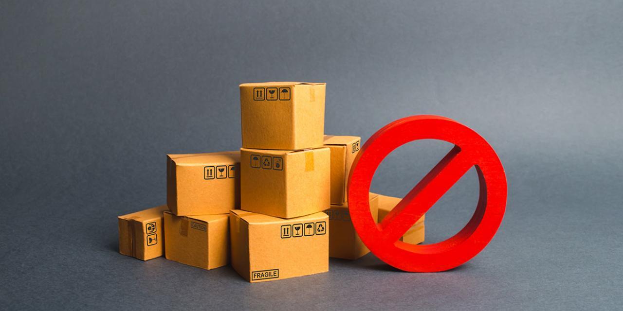 Gestapelte Kartons und ein dreidimensionales Verneinungssymbol