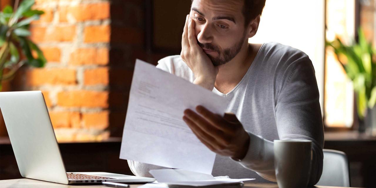 Junger Mann liest besorgt ein Schreiben