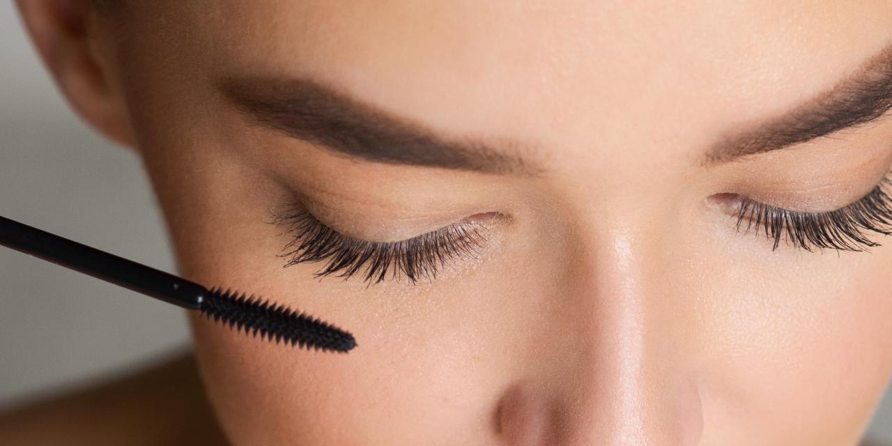 Dame mit geschlossenen Augen hält Mascara vor ihren WImpern