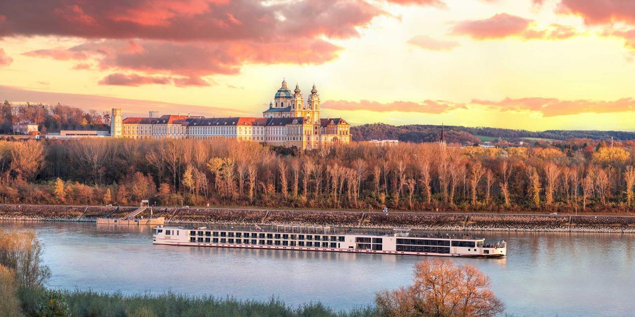 Kreuzfahrtschiff auf Donau vor dem Stift Melk und Herbstwald am Ufer