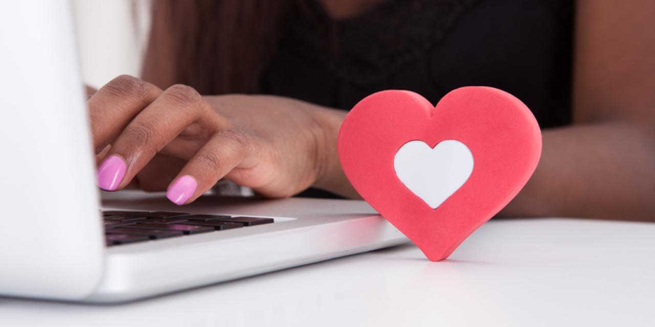 Frau tippt am Laptop, im Vordergrund Herzdekoration