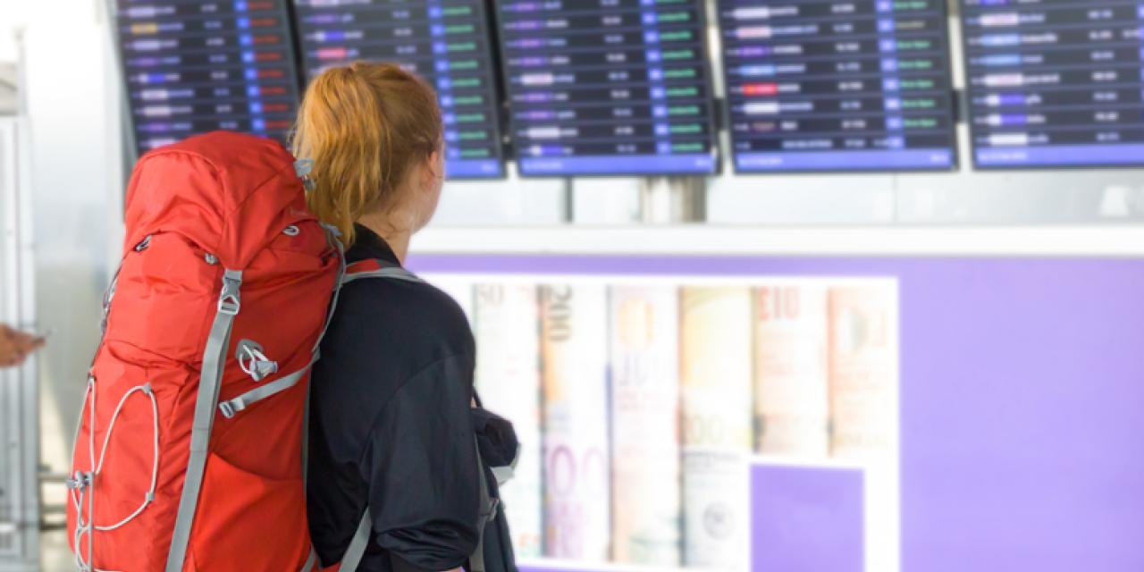 Junge Rucksacktouristin betrachtet Abfluganzeige am Flughafen