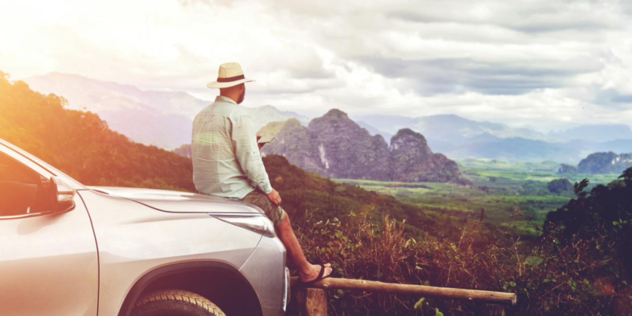 Man with hat leaning on the bonnet of a parked car and enjoying the distant view