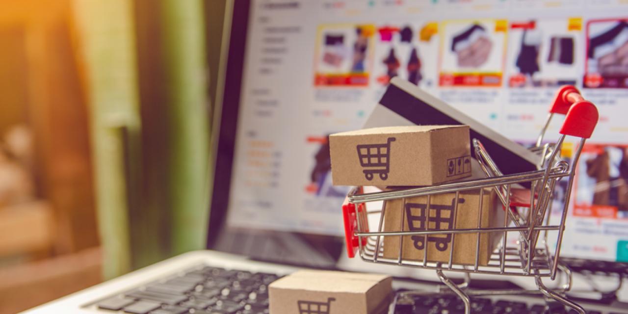 Modell eines mit Paketen befüllten Einkauswagens vor Bildschirm eines Laptops, der eine Webshopseite zeigt