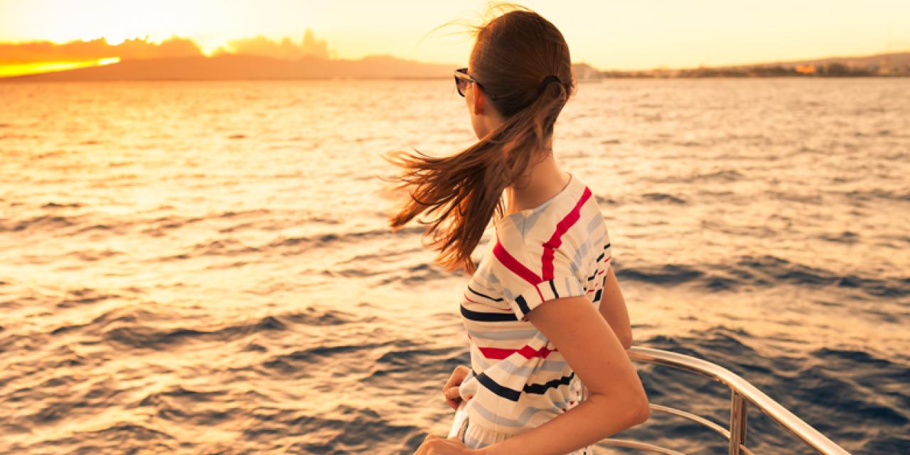 junge Frau am Bug eines Schiffes