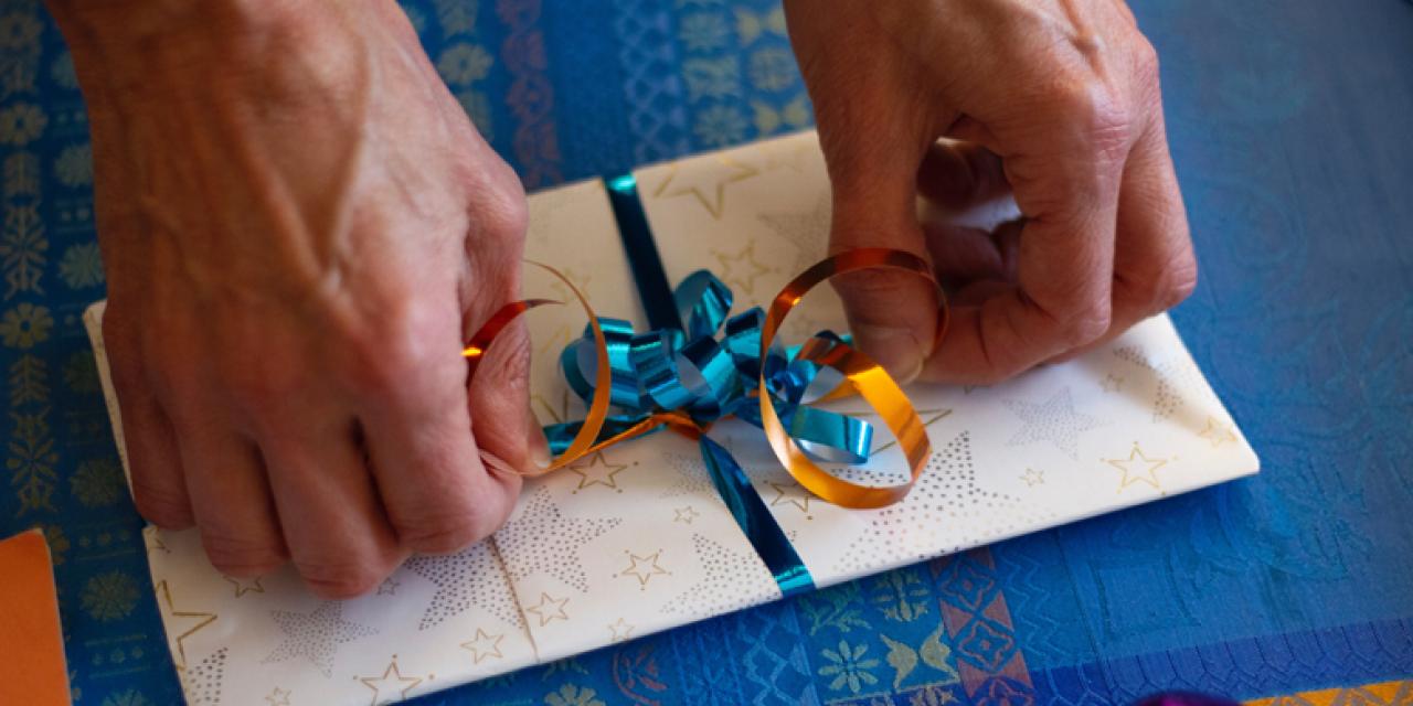 Männerhände binden dekorative Schleife um einen Briefumschlag