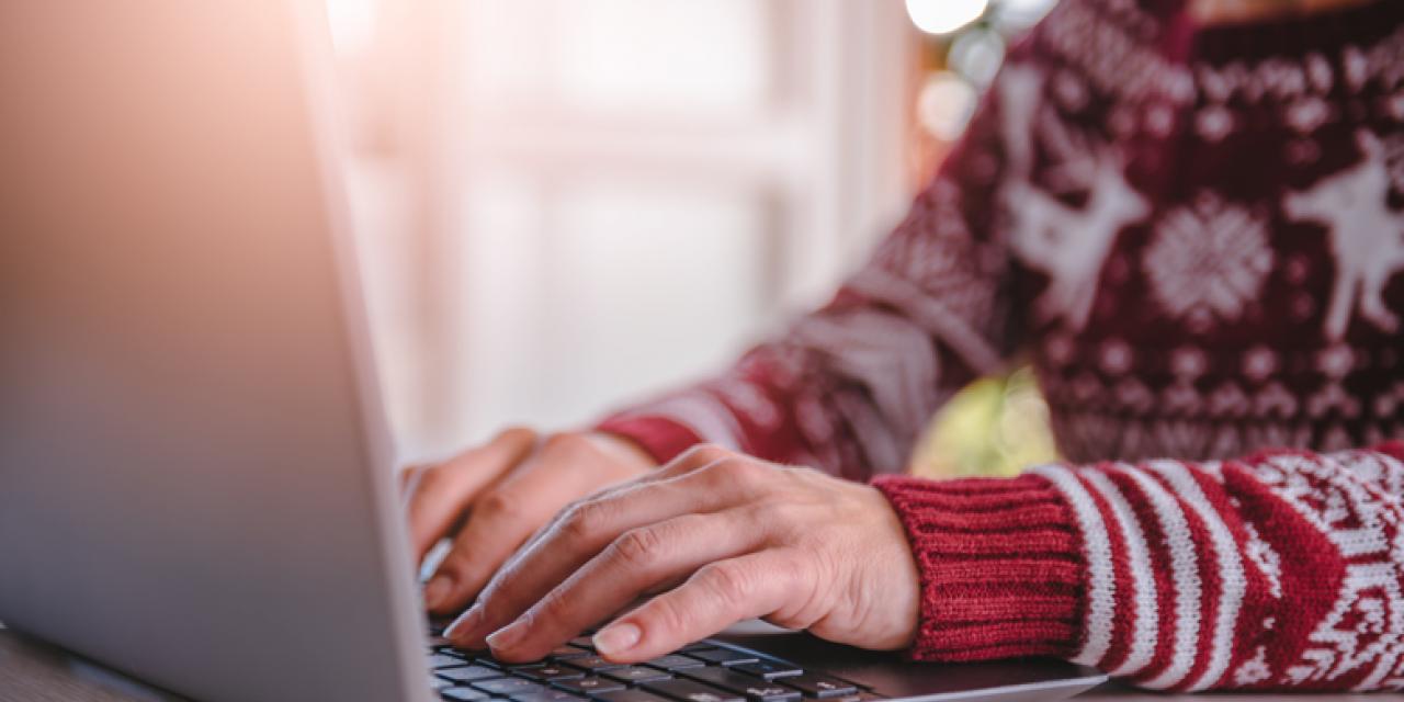 Rückseite eines Laptops, Torso einer tippenden Frau im Pullover