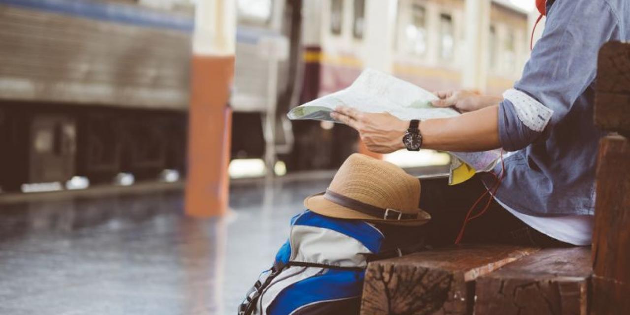 Lesender Mann mit Gepäck am Bahnsteig