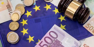 Euro notes and coins and a court hammer lie on European flag