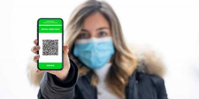 Junge Frau hält Handy dem Betrachter Hanndydisplay mit QR des Grünen Passes entgegen