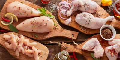Hühnerfilets, Hühnerkeulen und Hühnerflügel auf einem Tisch mit Zwiebeln und Gewürzen