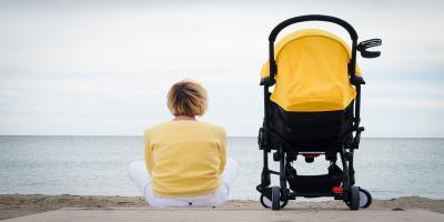 Frau sitzt am Strand und blickt aufs Meer. Gelb-schwarzer Buggy steht links neben ihr.