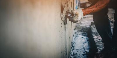Maurer zieht nasse Fassade mit Kelle ab