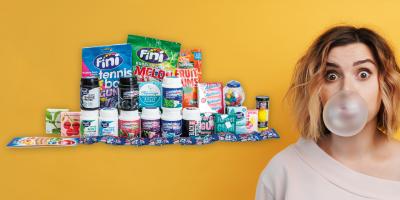 Frau mit Kaugummiblase vor dem Mund vor gelbem Hintergrund, links im Bild Kaugummipackungen.