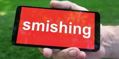 Hand holding mobile phone with lettering SMISHING on red background