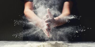 Mehl auf dem Tisch - Person reibt sich die mehligen Hände