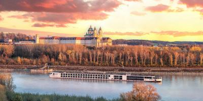 Cruise ship on the Danube in front of Melk Abbey and autumn forest on the bank