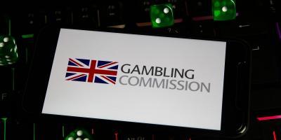 """Smartphone Display zeigt """"Gambling Commission"""" und britischer Flagge, im Hintergrund Tastatur und Spielwürfel"""
