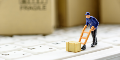 Figure of a parcel delivery man with sack truck and parcel