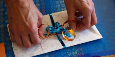Men's hands tie decorative bow around an envelope