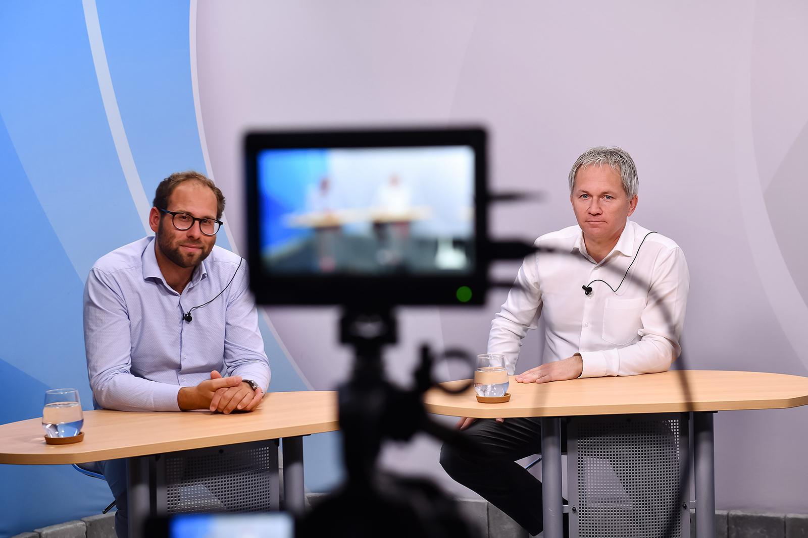 Zwei der Panelteilnehmer, die vor der Kamera an einem Tisch sitzen.