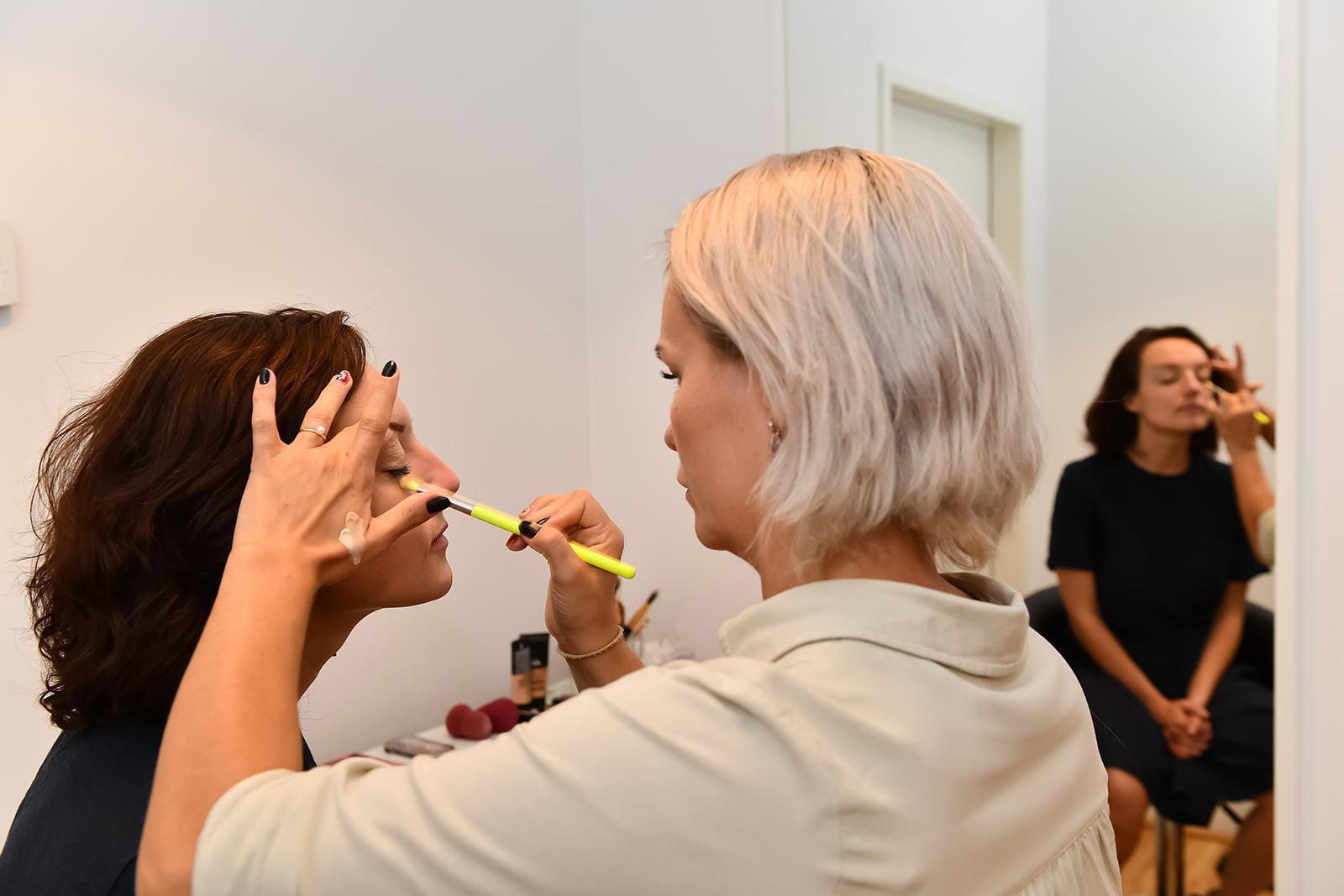 Eine Dame wird in der Maske geschminkt.