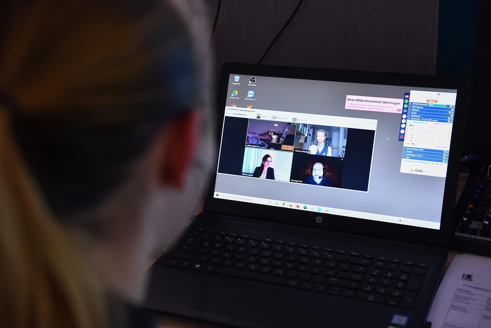 Eine Dame, die auf einen Computerbildschirm schaut. Auf diesem ist ein Videocall zu sehen.