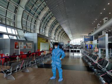 Leerer Flughafen während der Pandemie, Mann mit Schutzanzug
