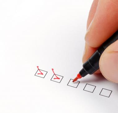 Nahaufnahme einer Hand mit Stift, die Checkboxen abhakt