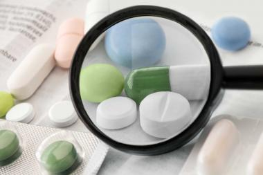 Tabletten und Beipackzettel, darüber Lupe