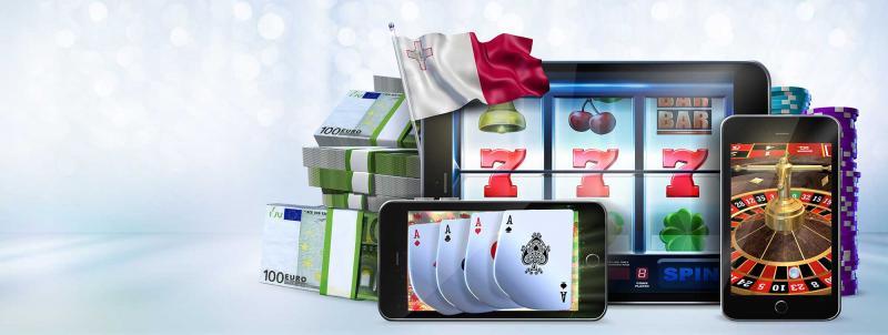 Mobile Geräte mit Glückspielen am Display, dahinter Geld- und Spielchipsstabel und eine Malta Flagge